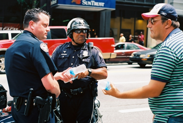 Street vendor offering water to policemen